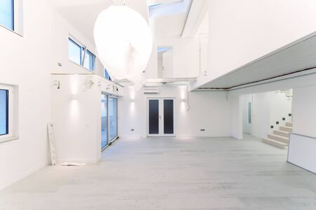 Photo for Interior of empty stylish modern open space two level apartment with white walls and large round chandelier in the middle ready to move in - Royalty Free Image