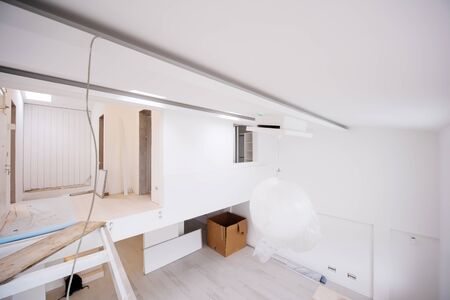 Photo pour Interior of empty stylish modern open space two level apartment with white walls and large round chandelier in the middle ready to move in - image libre de droit