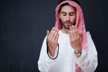 Photo pour young arabian man in traditional clothes making traditional prayer to God, keeps hands in praying gesture in front of black chalkboard representing modern islam fashion and ramadan kareem concept - image libre de droit