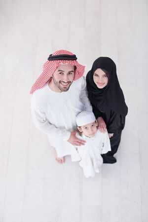 Photo pour top view portrait of young happy arabian muslim family couple with son in traditional clothes spending time together during the month of Ramadan at home - image libre de droit