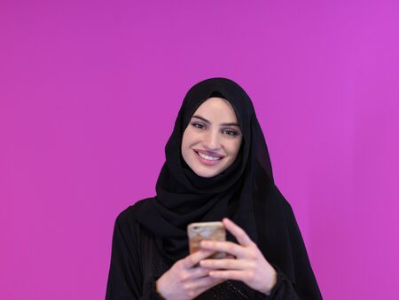Photo pour young modern muslim business woman using smartphone wearing hijab clothes isolated on pink background - image libre de droit