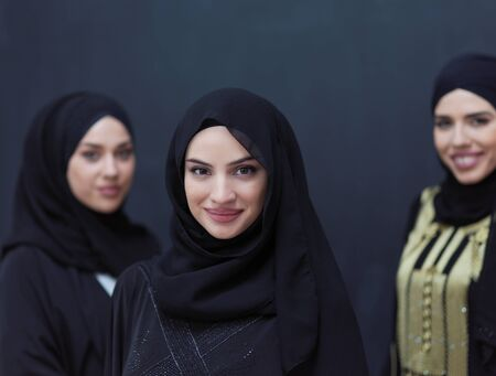 Photo pour group portrait of beautiful muslim women in fashionable dress with hijab isolated on black chalkboard background representing modern islam fashion and ramadan kareem concept - image libre de droit