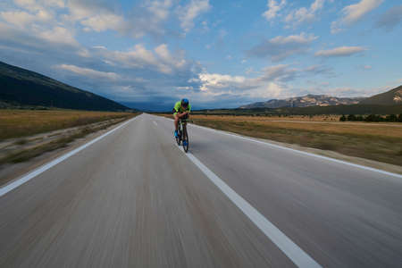 Photo pour triathlon athlete riding professional racing bike at workout on curvy country road - image libre de droit