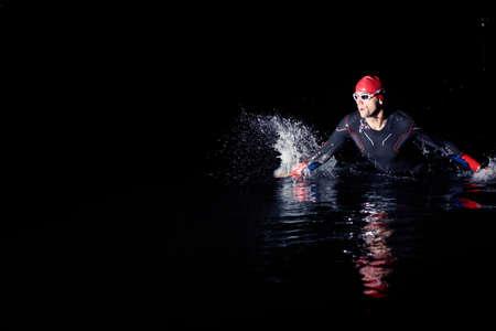 Photo pour triathlon athlete finishing swimming training at dark night - image libre de droit
