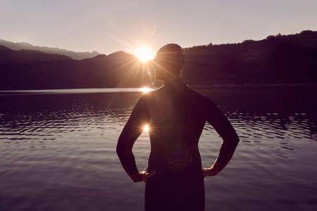 Photo pour triathlon athlete starting swimming training on lake - image libre de droit