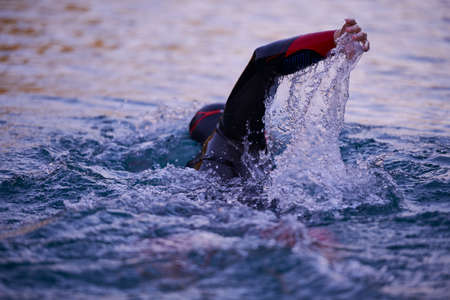 Photo pour triathlon athlete swimming on lake in sunrise wearing wetsuit - image libre de droit