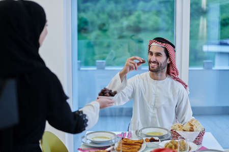 Photo pour Muslim couple sharing dates for starting iftar - image libre de droit
