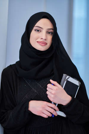 Young Arab businesswoman in traditional clothes or abaya with tablet computer