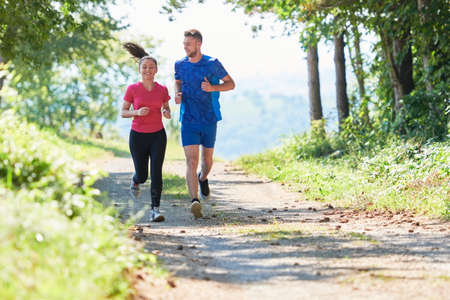 Photo for couple enjoying in a healthy lifestyle while jogging on a country road - Royalty Free Image