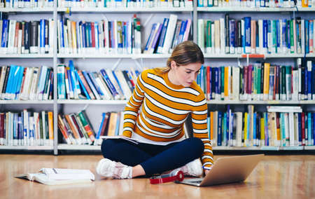 Photo pour the student uses a notebook and a school library - image libre de droit