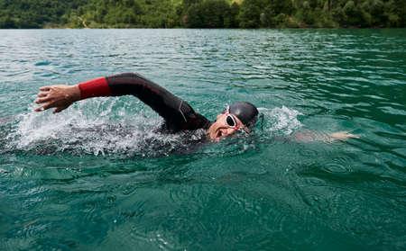 Photo pour triathlon athlete swimming on lake wearing wetsuit - image libre de droit
