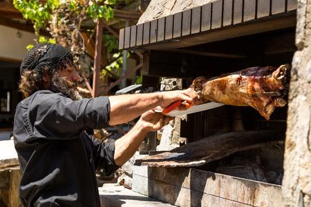 GREECE. CRETE. LASITHI PLATEAU. - AUGUST 2013: Greece farmer Dimitris threats friends roasted whole lamb, prepared on the grill.