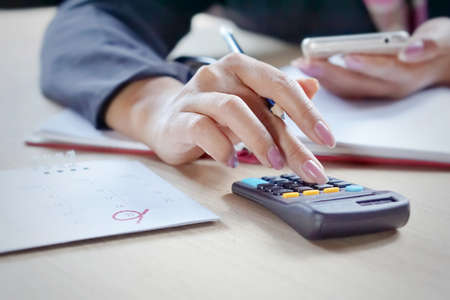 close view of a buisiness woman hand calculating her monthlty expenses during tax season.
