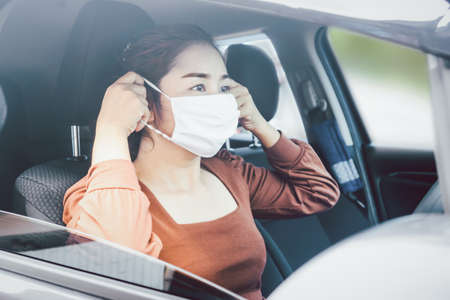 Photo pour Asian woman sitting in a car wearing protective mask before driving car during covid-19 pandemic, new normal lifestyle concept background - image libre de droit