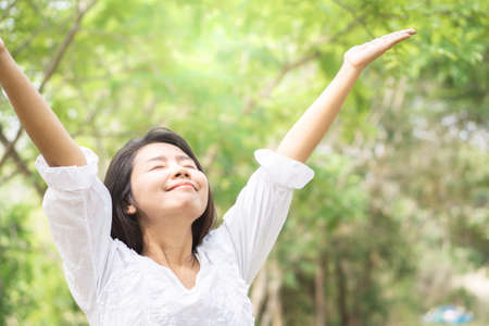 Photo for happy Asian woman arms up and breathing deep outdoors with nature background - Royalty Free Image