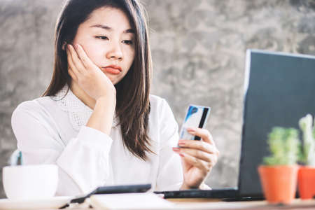 Photo pour sad Asian woman having problem with limit credit card for online shopping, over spending concept - image libre de droit