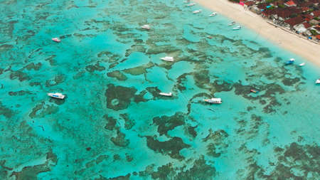 Photo pour Sea reefs off the coast of the village of Lembongan with boats on the island of Nusa Lembongan. Indonesia. Aerial view. - image libre de droit