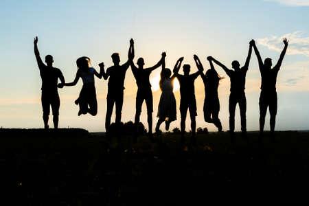 Photo pour Silhouettes of jumping friends on a sunset background. - image libre de droit