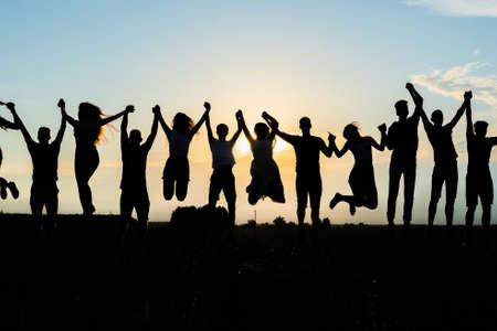 Foto für Silhouettes of jumping friends on a sunset background. - Lizenzfreies Bild