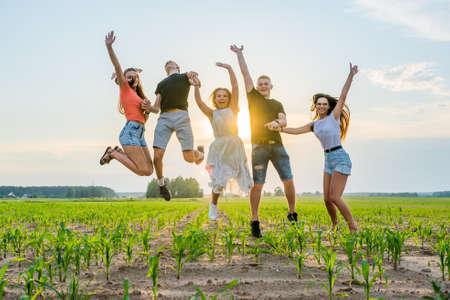 Foto de Friends are jumping holding hands at sunset. - Imagen libre de derechos