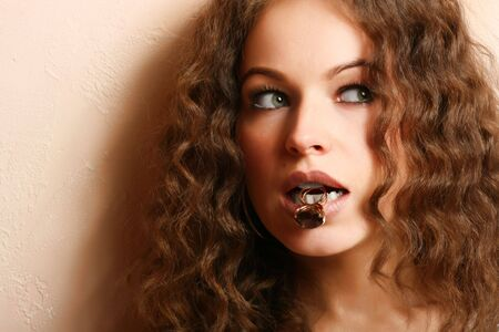 Jewelry and Beauty. Beautiful woman holding a ring in a teeth