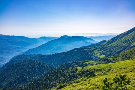 Photo for View over the Green Valley, surrounded by high mountains on a summer sunset. Layers of mountains in the haze during sunset. Multilayered misty nountains. Mountains in the summer. - Royalty Free Image