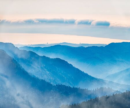 Green mountain slope. Layers of mountains in the haze during sunset. Multilayered misty nountains. Krasnaya Polyana, Sochi, Russia.