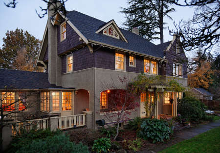Exterior view of a large home with lots of trees and greenery in the evening. Horizontal shot.