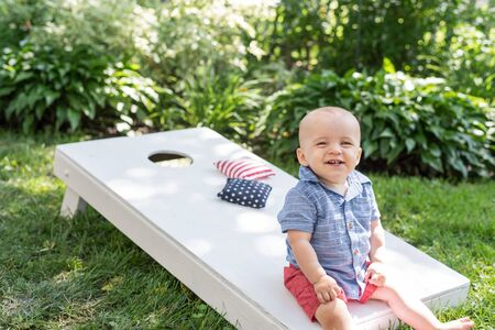 Photo for happy boy playing cornhole game in backyard on 4th of July - Royalty Free Image