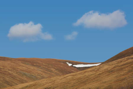 Patch of Snow on Hill top with cloudy blue sky