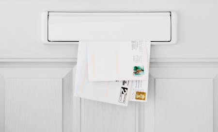 Photo pour Three letters in a letterbox inside a white front door - image libre de droit