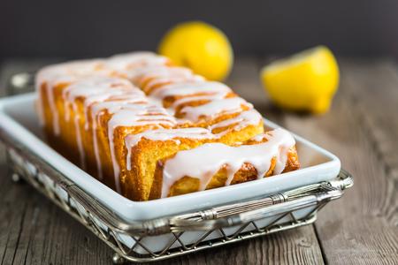 Photo pour Lemon yogurt loaf cake, sliced on a creative plate on wooden background for your design - image libre de droit