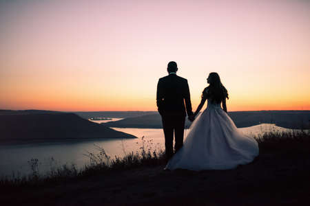 Photo pour Silhouettes of bride and groom in wedding dress at night against backdrop of large lake and islands. Bakota, Ukraine - image libre de droit