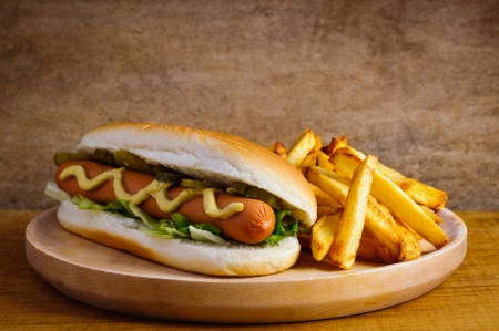 Hot dog with french fries on a wooden plate