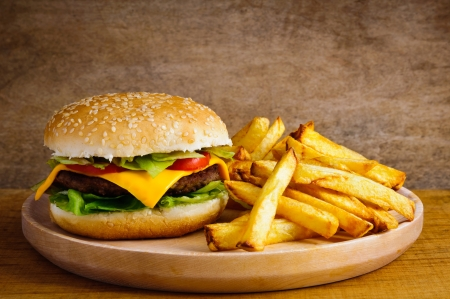 Fast food hamburger and french fries on a wooden plate