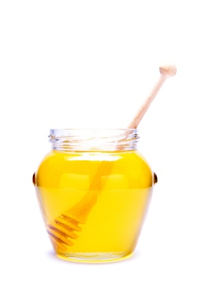 glass of honey with wooden dipper isolated on a white background