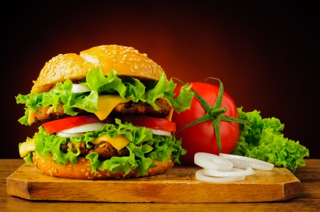 Foto de still life with double cheeseburger or hamburger and fresh vegetables - Imagen libre de derechos