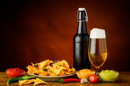 still life with nacho tortilla chips, cheese, salsa guacamole dip and beer