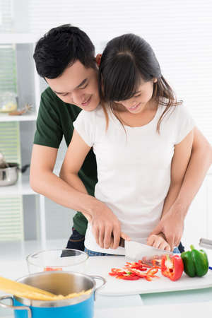 Couple bonding while cooking together in the kitchen