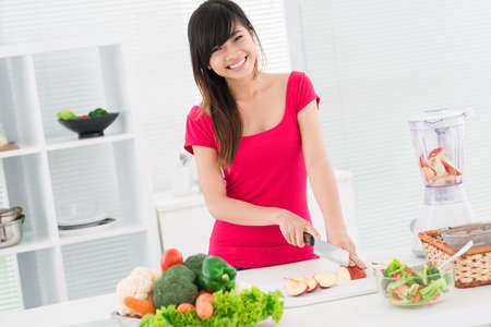 Lovely girl preparing low-calorie snack from fresh fruit and vegetables