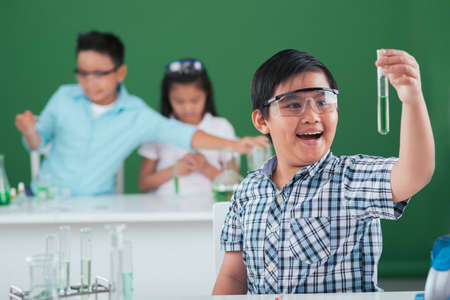 Happy excited boy looking at the test tube with chemical reagent