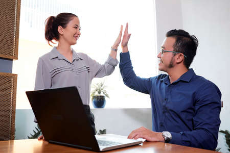 Photo for Happy Vietnaemse business colleagues giving each other high five to express unity - Royalty Free Image