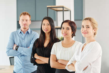 Photo for Portrait of young multi-ethnic business team standing together with arms crossed and smiling at camera at office - Royalty Free Image