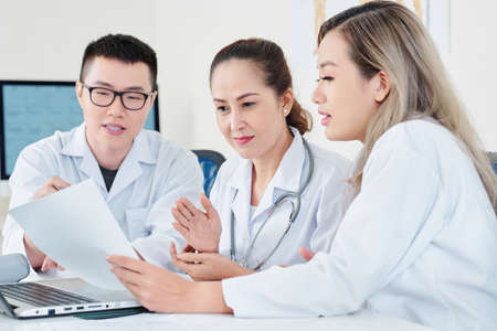 Photo pour Team of experienced Asian doctors reading document and discussing medical history of patient at meeting - image libre de droit