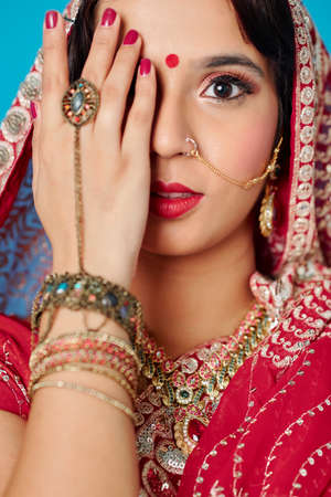 Photo for Beautiful Indian woman covering her face with hand with many bracelets and big ring and looking at camera - Royalty Free Image