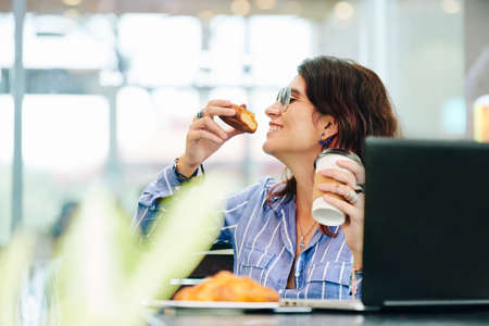Photo pour Happy young woman enjoying delicious pastry and cup of fresh coffee in local caffeteria - image libre de droit