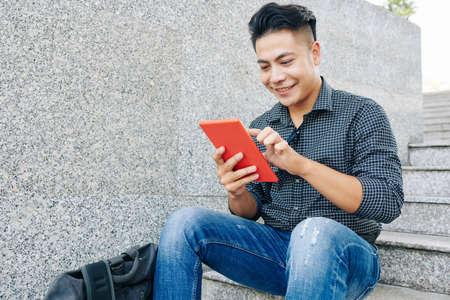 Foto de Portrait of young handsome Asian man resting outdoors and using application on table computer - Imagen libre de derechos