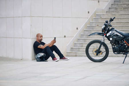 Photo pour Muscular man in black clothes sitting on ground and texting friends after riding motorcycle - image libre de droit