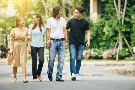 Photo for Happy Vietnamese middle-aged parents and adult children walking in the street and discussing news - Royalty Free Image