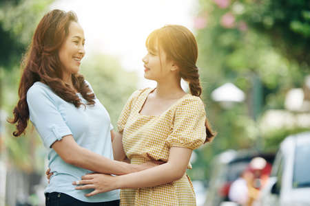 Photo for Happy mature Vietnamese woman looking at her smiling beautiful adult daughter - Royalty Free Image